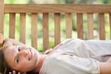 Smiling woman lying on a park bench