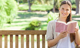 Smiling woman reading a book on a park bench