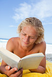 Serious man lying on his beach towel while reading a book