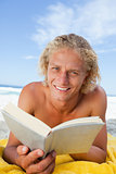 Smiling blonde man reading a book while lying on the beach