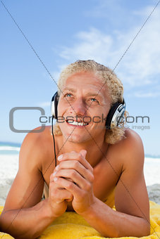 Smiling man looking up while listening to music with his headset