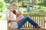 Side view of a smiling woman sitting on a park bench with her bo