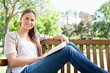 Smiling woman sitting on a bench with a book
