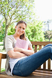 Smiling woman sitting on a park bench with her book