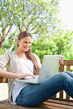 Smiling woman with her laptop sitting on a bench