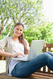 Smiling woman with a laptop sitting on a park bench