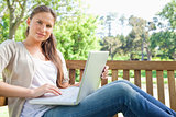 Woman with a laptop sitting on a park bench