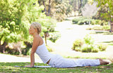 Side view of a woman doing stretches on the grass