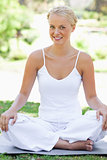 Smiling woman in a yoga position on the grass