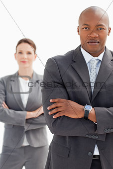 Businesswoman stands behind businessman