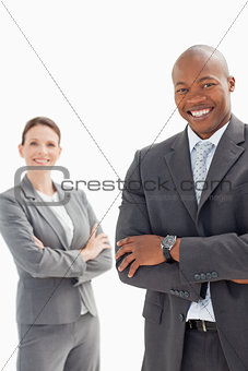 Smiling businessman and woman with folded hands