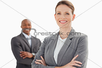 Smiling businesswoman and man with arms crossed