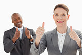 Smiling business people with thumbs up