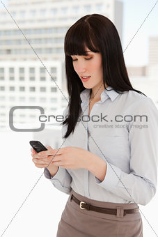 A woman at work uses her phone to text