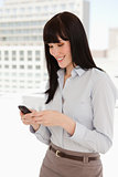 Smiling woman at work sending a text message