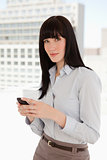 Woman looking in front of her as she sends a text