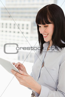 A happy woman using her tablet pc in her office