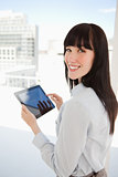 Woman looking into the camera as she holds a tablet pc in her ha