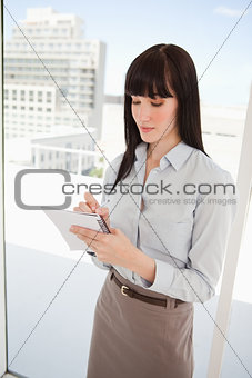 A woman with a note pad writing down some notes