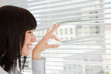 A smiling woman looks out through her blinds