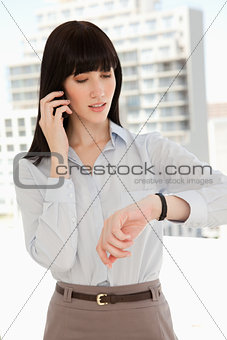 A woman making a quick call as she checks the time
