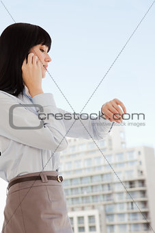 A business woman makes a phone call as she looks at the time