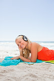 Young blonde woman lying down while listening to music