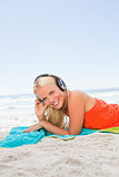 Young smiling woman lying on her beach towel while listening to 