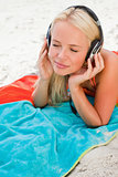 Young woman closing her eyes while listening to music on her bea