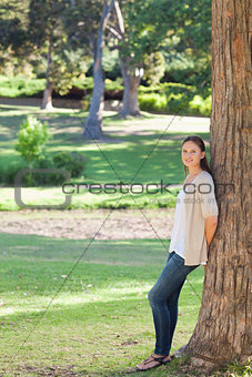 Woman in the countryside leaning against a tree