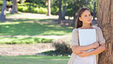 Woman holding a laptop while leaning against a tree
