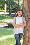 Smiling woman holding a laptop while leaning against a tree