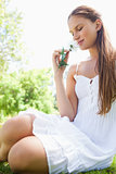 Woman smelling a flower while sitting on the lawn