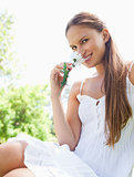 Smiling woman in the park smelling a flower