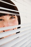 A woman looking through blinds she has opened slightly