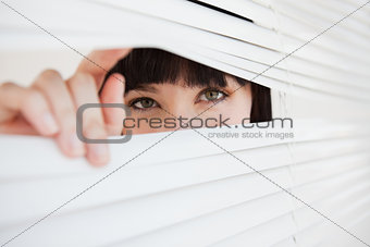 A woman opening a part of closed blinds with her fingers