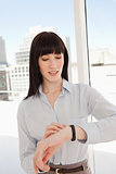A business woman checks the time with her watch