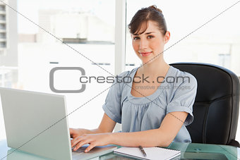 A smiling employee sits at her desk with her laptop