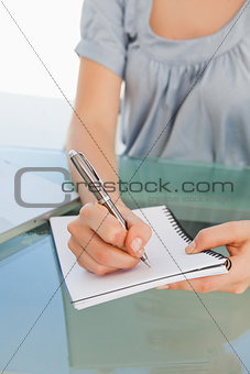 Close up of a woman writing on a notepad