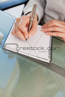 Close up of a woman jotting down some notes