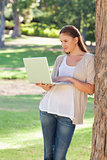 Woman using a notebook while leaning against a tree