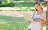 Woman leaning against a tree while using a laptop