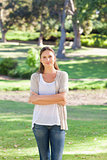 Woman with her arms folded standing in the park