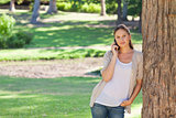 Woman on the phone leaning against a tree