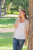 Woman talking on the phone while leaning against a tree