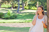 Woman talking on her cellphone while leaning against a tree