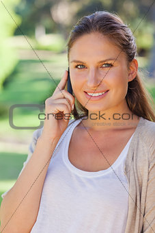 Close up of smiling woman on her cellphone in the park