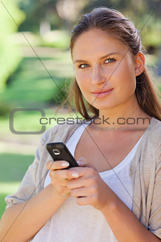 Close up of woman holding her cellphone in the park