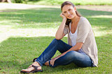 Smiling woman sitting on the grass