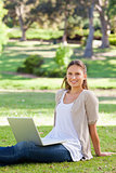 Smiling woman with her laptop sitting in the park